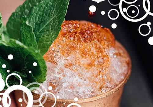 Cocktail mit Minzblatt in einer Hand